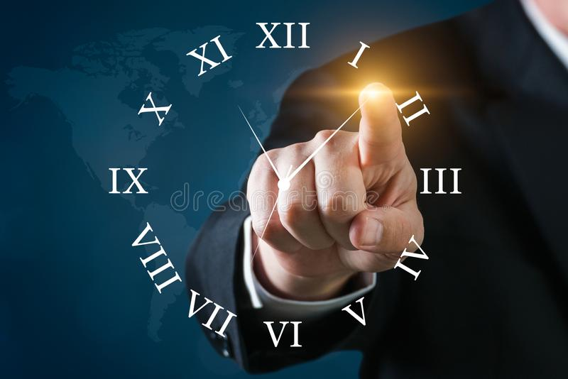 Business man touching a clock with world map on a blue background stock photography