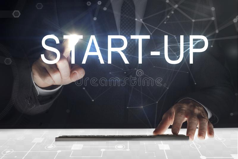 Business man touching screen with `Start-up` writing royalty free stock photo