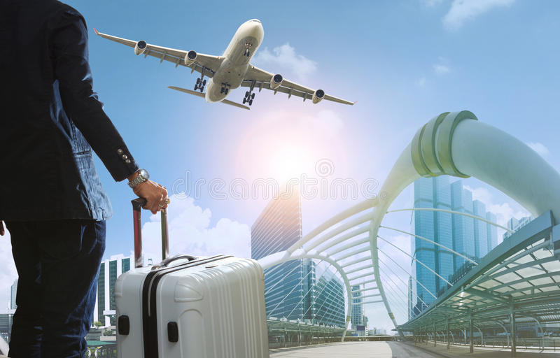 business man and traveling luggage in city life with plane flying over skyscraper stock photography