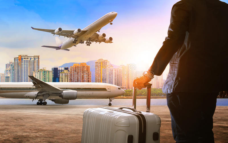 Business man and traveling luggage standing in airport and passe. Nger plane flying above royalty free stock photo