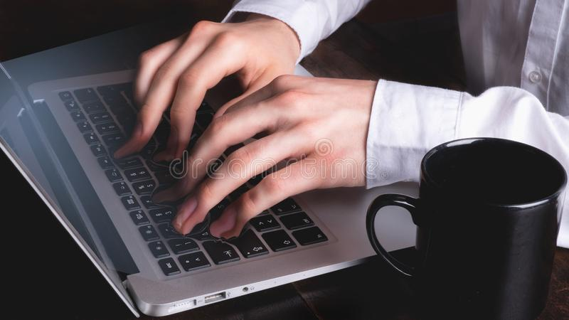 Business man typing on laptop keyboard while fingers and keys fuse - surreal stock images