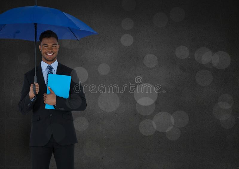 Business man with umbrella and blue book against grey wall and bokeh stock images