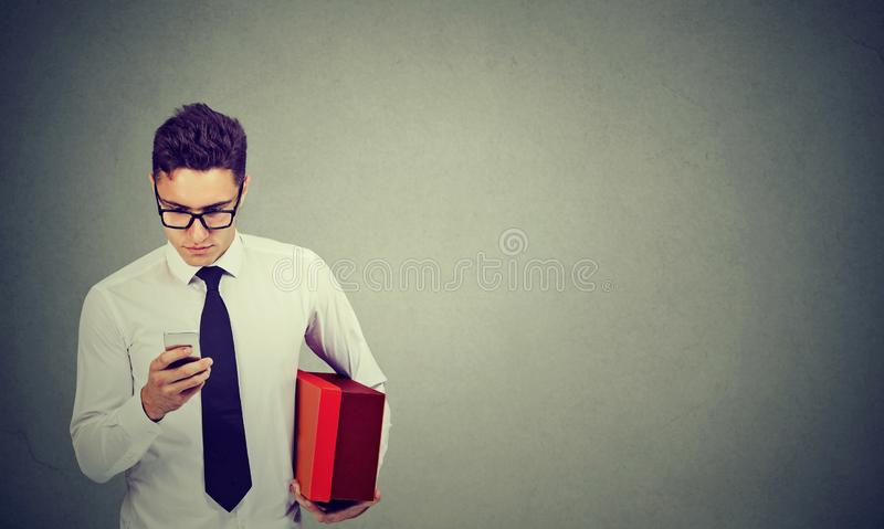 Business man using cellphone holding a delivery box royalty free stock photo