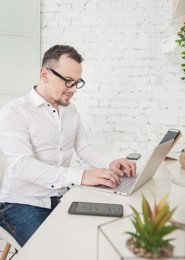 Business man using laptop at home smiling. Freelance or distance study concept stock images