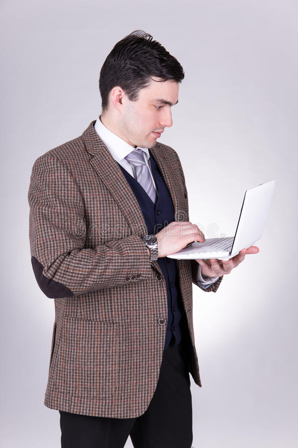 Business man using laptop over grey stock image