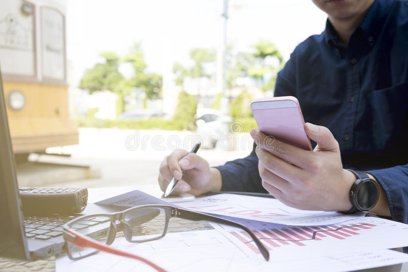 Business man using laptop and smartphone for analytic financial graph year 2017 trend forecasting planning outdoor pla. Business man using laptop and smartphone stock images
