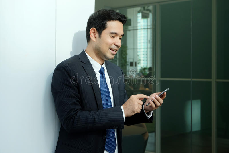 Business man using smart phone with happy smiling face standing stock image