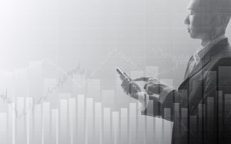 Business man using smartphone with abstract financial chart and up trend line graph in stock market on black and whit color backgr. Business man using smartphone stock photos
