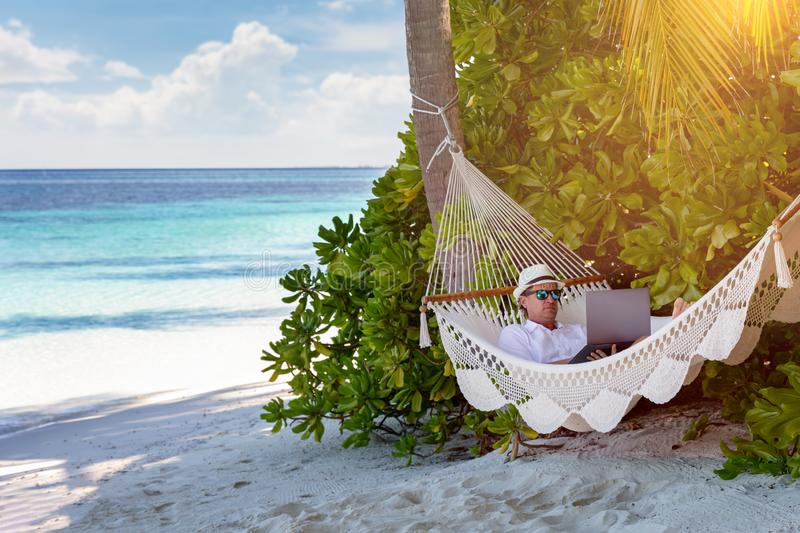 A business man on vacation works on his laptop on a tropical beach stock photography