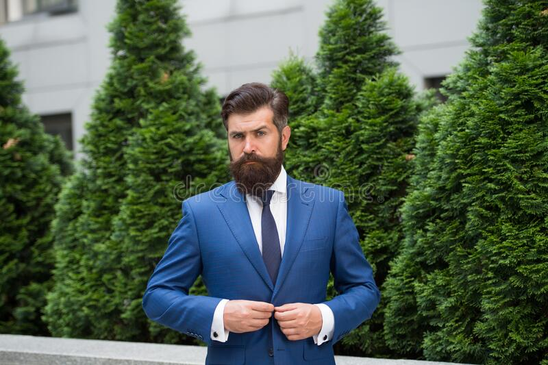 Business man walking outdoor. Businessman In Nature. energy efficiency concept. bearded man in jacket near cypress tree. Handsome man smartly dressed. ceo walk stock photography