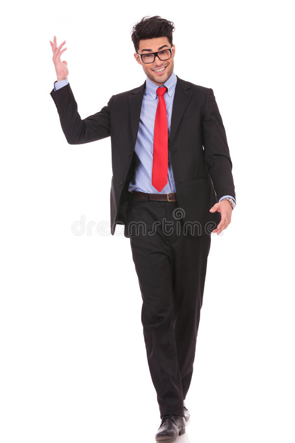 Business man walking towards you. Full length picture of a young business man walking forward with one of his hands in the air and smiling to the camera on white royalty free stock image