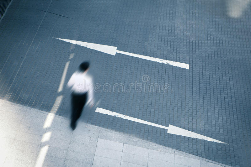 Business man walking with two arrows royalty free stock photography