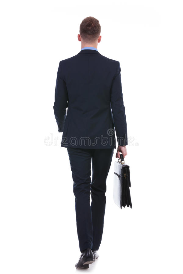 Business man walks away with suitcase royalty free stock photography