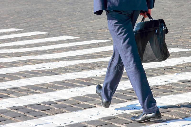Business man walks on a pedestrian crossing. Goal and success stock photography