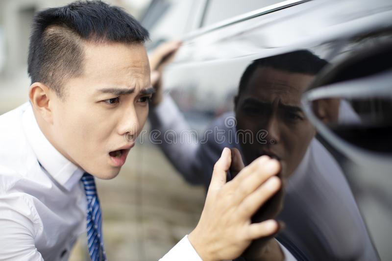 Business man watching new car and worry it. Young business man watching new car and worry it royalty free stock photos
