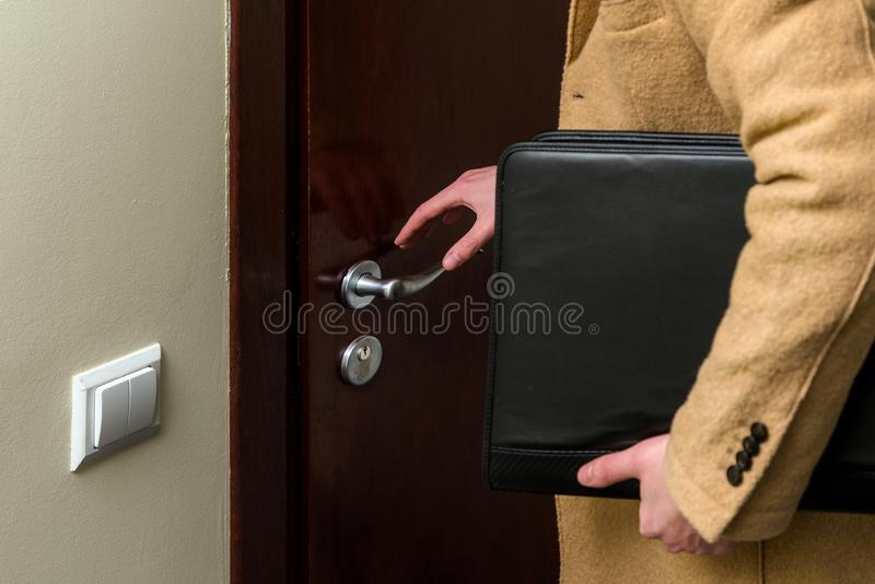 Business man wearing a luxury brown coat and holding leather lap stock photo