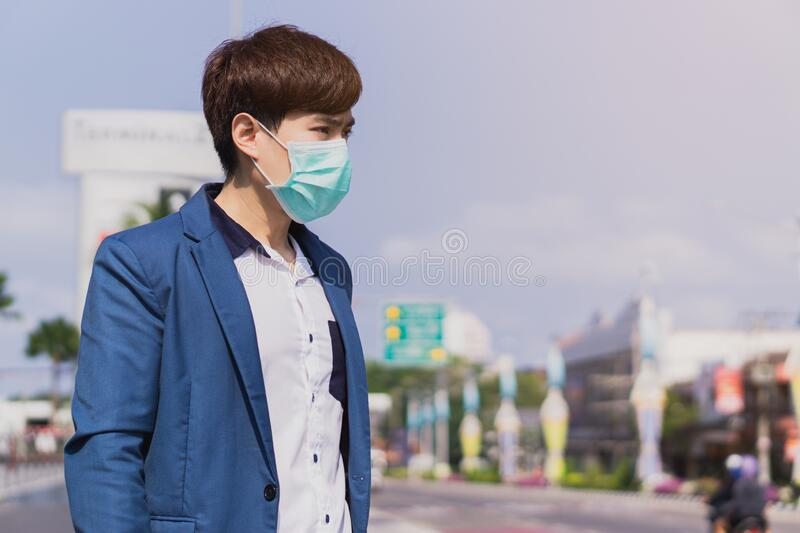 The business man wearing protection face mask against coronavirus, PM 2.5 and cold while standing on escalator. Coronavirus and. Air pollution pm 2.5 concept stock photo