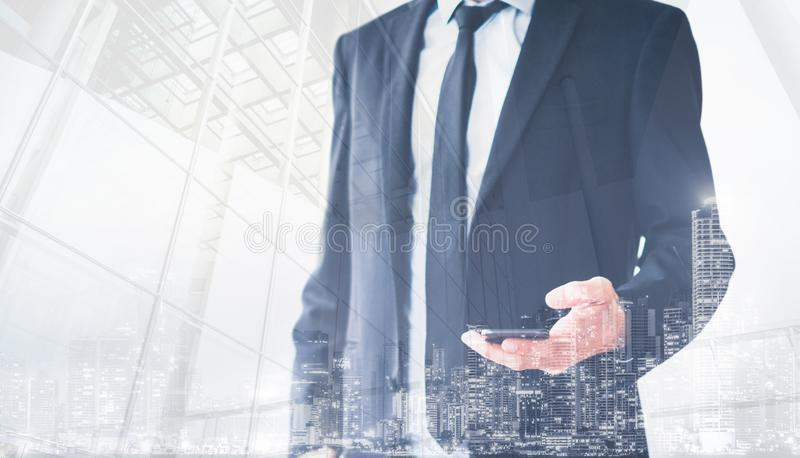 Business man wearing suit holding mobile phone double exposure with city background royalty free stock photos