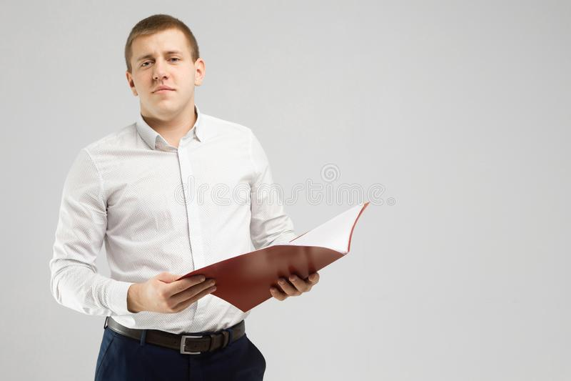 Young man with an open folder in his hands isolated on a light background royalty free stock photo