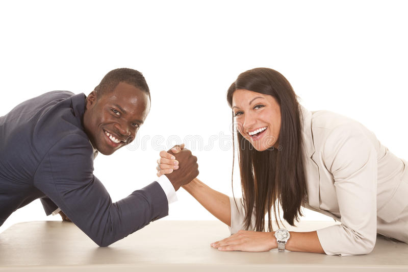 Business man and woman arm wrestle laugh looking. A business men and women arm wrestling with smiles on their faces stock photos