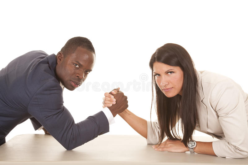 Business man and woman arm wrestle serious looking. A business men and women arm wrestling with serious expressions on their faces stock images