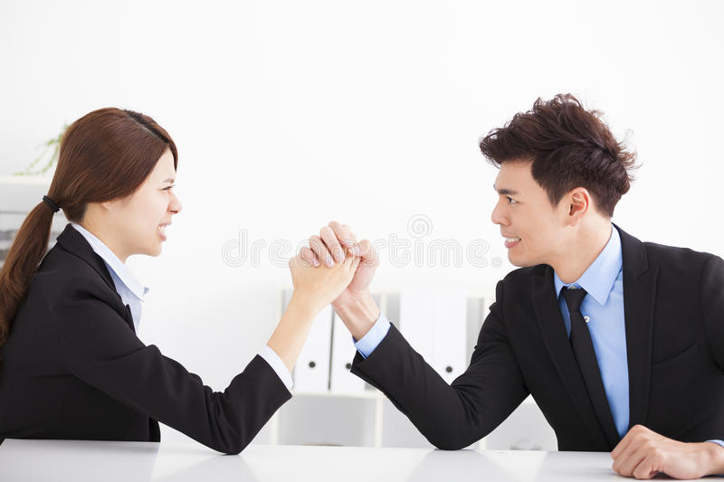 Business man and woman arm wrestling. Business men and women arm wrestling on desk in office royalty free stock image