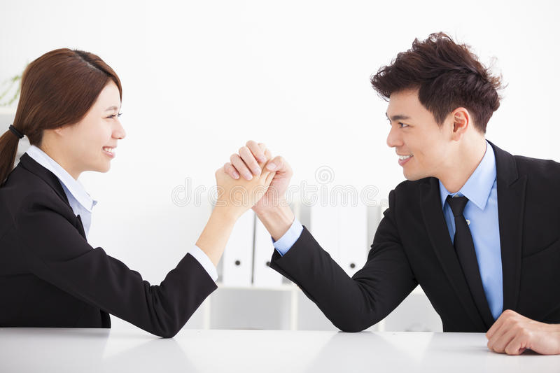Business man and woman arm wrestling. Business men and women arm wrestling on desk in office stock photography