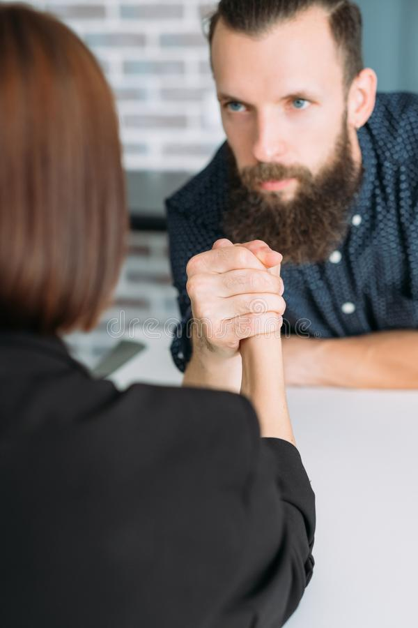 Business man woman arm wrestling office conflict. Business men and women arm wrestling at table. power control and office conflict stock image