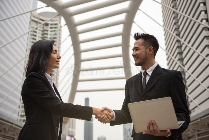 Business man and woman handshake stock images