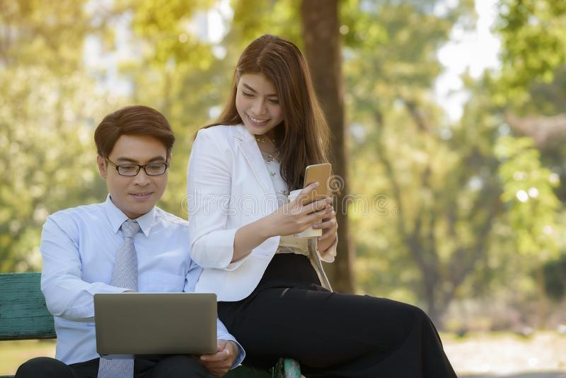 Business man and woman are interested in working on his laptop while relaxing in the park stock photography