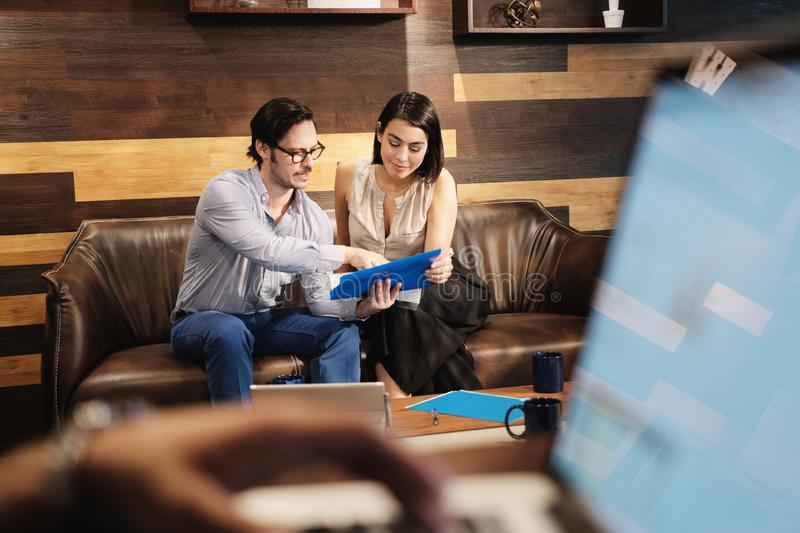 Business Man And Woman Meeting At Work In Office Cafeteria. Young male manager working in modern office cafeteria and meeting female colleague. Busy business men stock image
