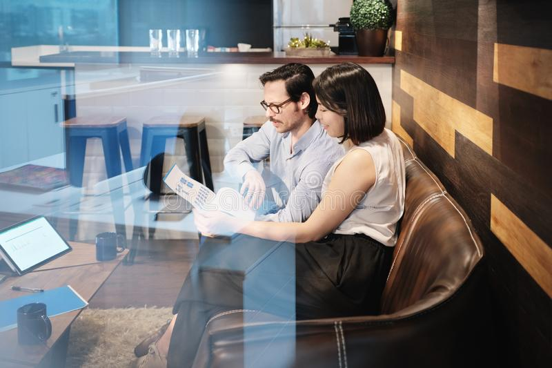 Business Man And Woman Meeting At Work In Office Cafeteria. Young male manager working in modern office cafeteria and meeting female colleague. Busy business men stock photo