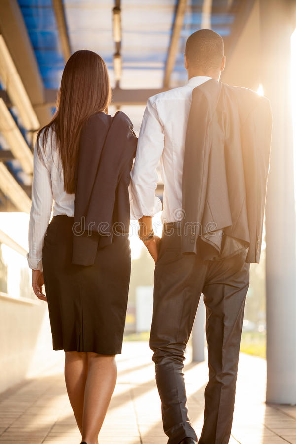 Business man and woman outdoors , over office building stock photography