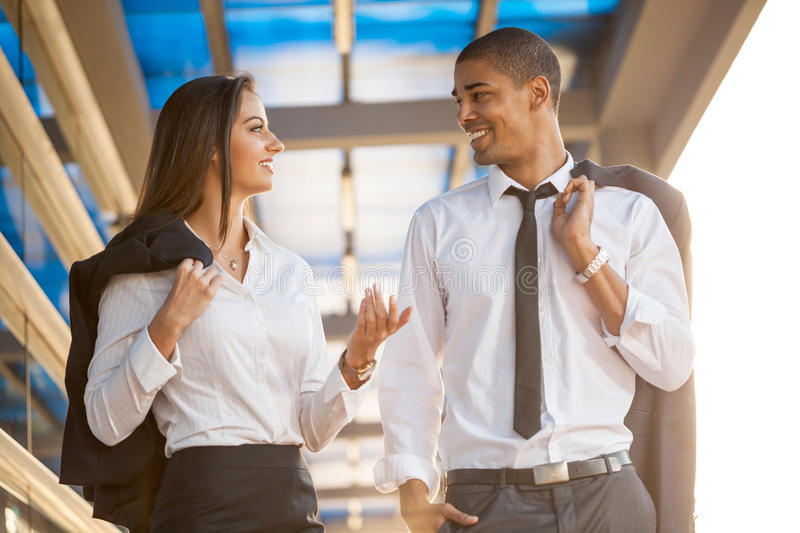 Business man and woman outdoors , over office building. Smiling business men and women on break ,walking around and talking stock images