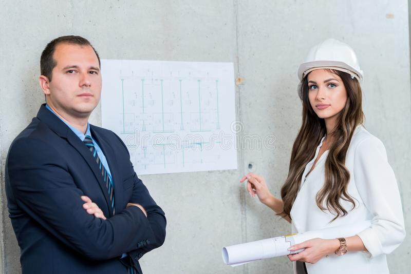 Business man and woman presenting architect blueprint. Making pr stock image