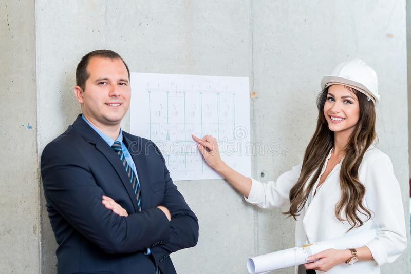 Business man and woman presenting architect blueprint. Making pr stock photography