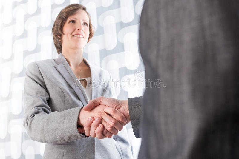Business man and woman shaking hands. Low angle view from behind the man of a business man and woman shaking hands on a deal or agreement , in welcome or in royalty free stock photography
