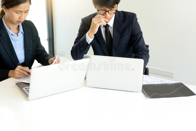 Business man and woman sit at ther table looking at computer laptop. Business men and women sit at ther table looking at computer laptop in the office , they stock image