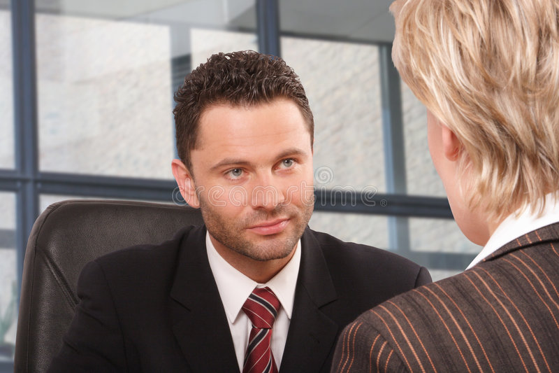 Business man and woman talk. White business man and woman talking in the office building stock image