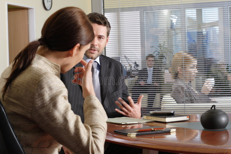 Business man and woman talking in the office. Other people in the background royalty free stock images