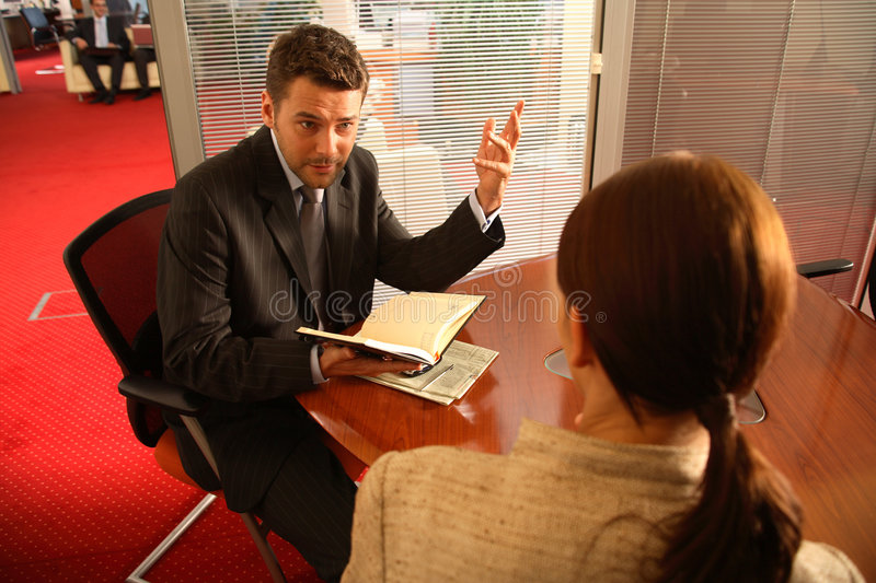Business man and woman talking in the office. Business man and woman sitting at the desk in the office and having meeting stock images