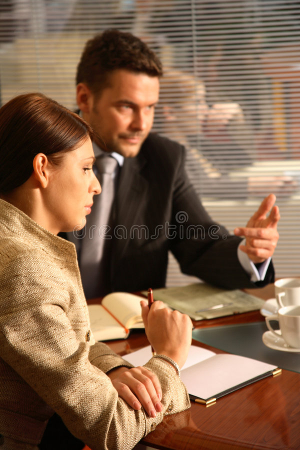 Business man and woman talking in the office. Business man and woman sitting at the desk in the office and having meeting,other woman in the background royalty free stock photography
