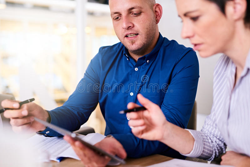 Business man and woman working on their computer together stock photos