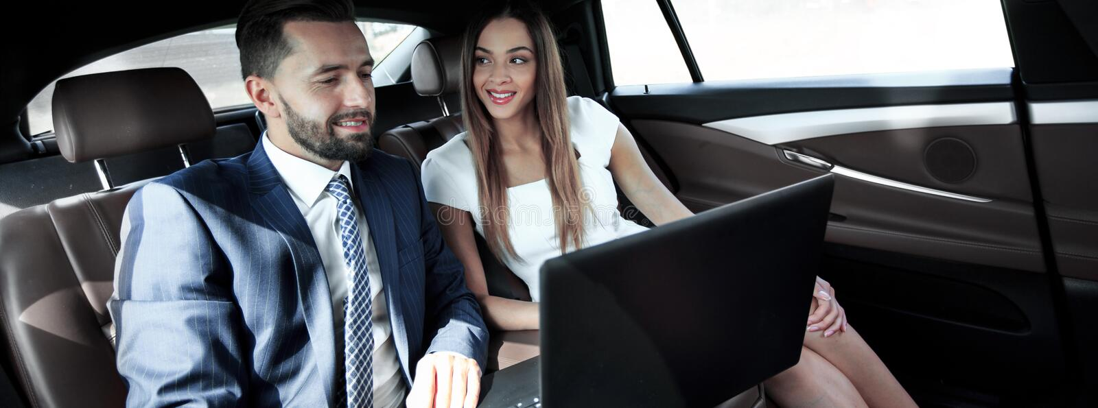 Business man and woman working together in the car. Business people with a laptop working in the back seat of a car stock images