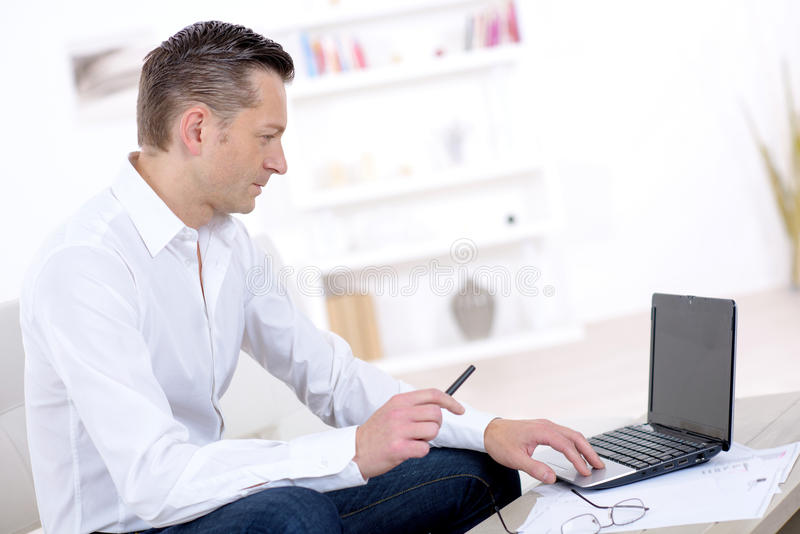 Business man working at home using laptop. Business man working at home using his laptop stock photography