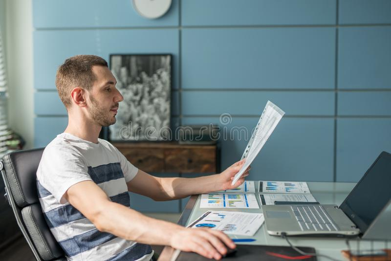 Business man working on a laptop at his desk in the office royalty free stock image