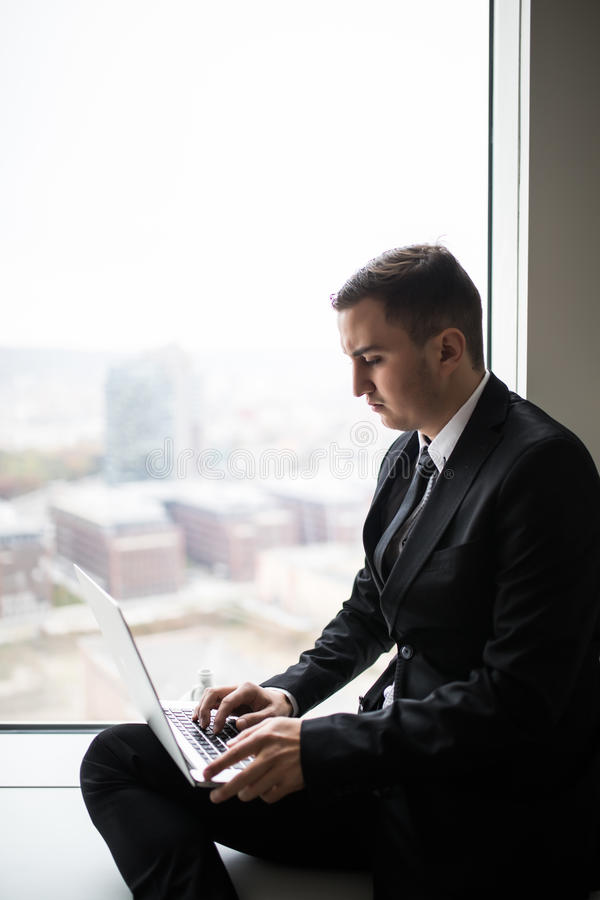 business man working near panoramic city window on laptop royalty free stock photo