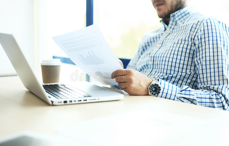 Business man working at office with laptop and documents on his desk. Analyze plans, papers, hands keyboard. Blurred background, film effect stock photo