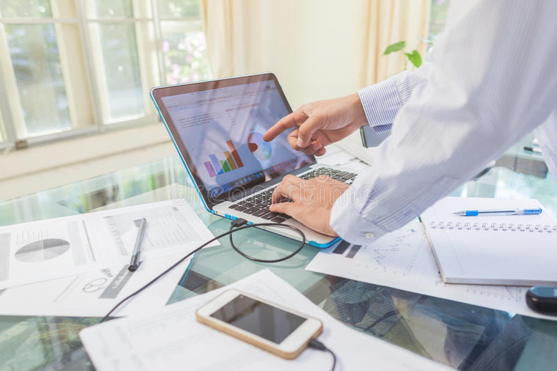 Business man working on open laptop at home office. Workplace stock photography