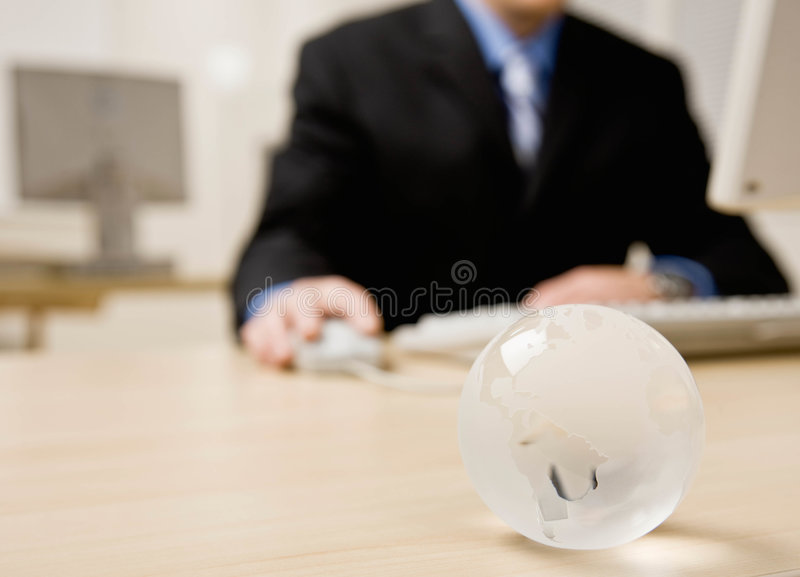 Business man works on desk top computer. Close up of glass globe on businessman�s desk royalty free stock photos